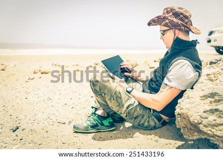 Young hipster man sitting in desert road - Concept of modern technologies with a alternative travel lifestyle - Overexposed vintage desaturated filtered look with focus on the hand using the laptop  - stock photo