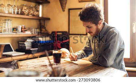 Young hipster man sketching on a notebook in his studio on a rustic wooden table - stock photo