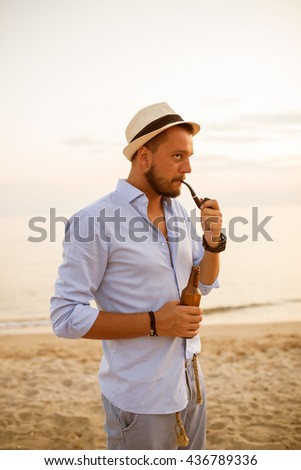 Young hipster man smoking pipe on the beach - stock photo