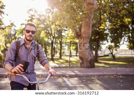 Young hipster man taking a break from riding his bike to drink coffee. Depth of field - stock photo