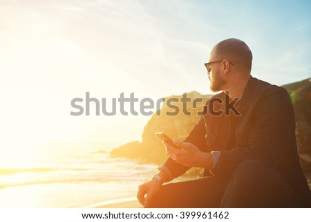 Young hipster man traveler with cell telephone in hand is enjoying amazing landscape, while is sitting on the beach near ocean with copy space background for your text message or advertising content - stock photo