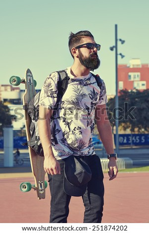 Young hipster man with a skateboard - stock photo