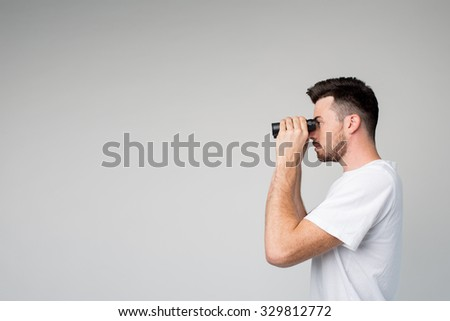 Young hipster  man with binoculars man isolated on light background - stock photo