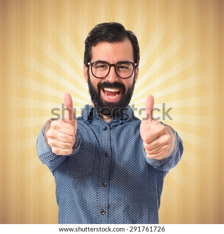 Young hipster man with thumb up over pop background - stock photo