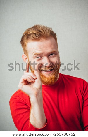 Young hipster red bearded Man showing small amount gesture - stock photo
