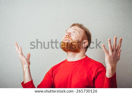 Young hipster red bearded Man with hands in the air - stock photo