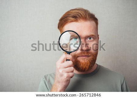 Young hipster red bearded man  with magnifying glass - stock photo