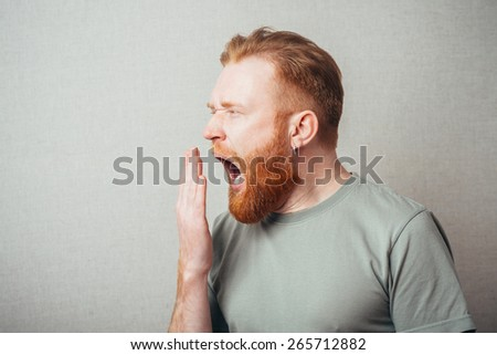 Young hipster red bearded man yawns - stock photo