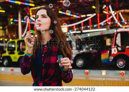 young hipster stylish beautiful woman blowing soap bubbles dressed in blue dress and checkered shirt at the amusement park, enjoying the summer day, fun, joy, happiness, mehndi drawing on hand - stock photo