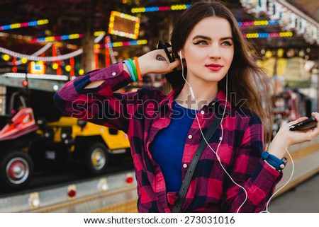 young hipster stylish beautiful woman listening to music on her mobile phone using earphones dressed in blue dress and checkered shirt at the amusement park, enjoying the summer day, cool accessories - stock photo