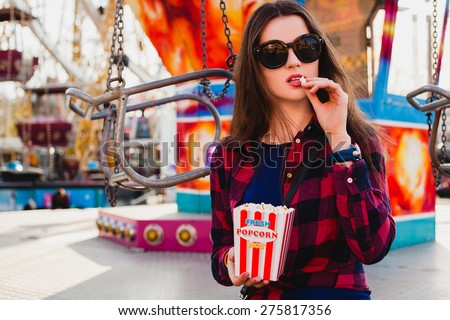 young hipster stylish beautiful woman sitting eating popcorn, dressed in blue dress and checkered shirt at the amusement park, enjoying the summer day, cool accessories, sunglasses, copyspace - stock photo