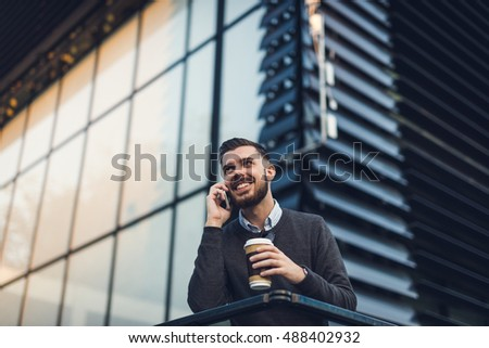 Young hipster talking on the phone and drinking coffee.