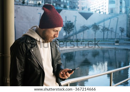 young hipster using on-line banking to his smart-phone.male student using cell phone outdoors.attractive bearded man typing a message on him digital smart-phone - stock photo