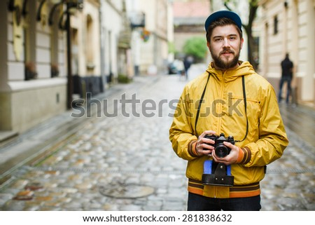 Young hipster with a beard holding oldshool film camera and looking at camera, on the street, wearing in bright raincoat and hat, portrait, day outdoors, ready to take a picture - stock photo