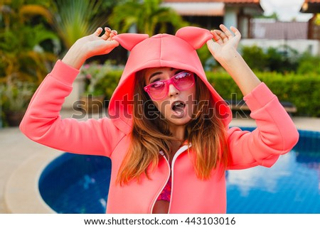 young hipster woman having fun, pool background, pink apparel, sunglasses, fun, summer, funny face, close up, expression, crazy, smiling - stock photo