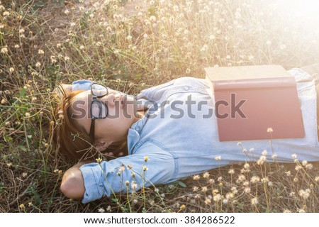 Young hipster woman lying in flower field after she tired for reading - stock photo