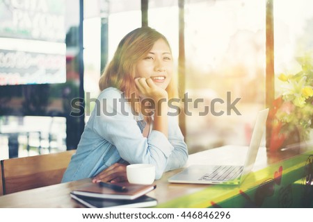Young hipster woman rest one hand on chin and smile enjoy in cafe.with reflection from windows