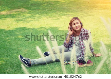 Young hipster woman sitting in the park enjoy listening music with headphone. - stock photo