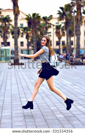 Young hipster woman traveling in miami california, jumping going crazy and having fun, mini skirt and crop top, travel with backpack, dancing, smiling, emotions, exotic palms. - stock photo