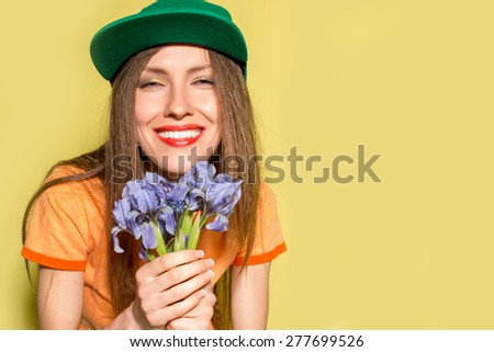 Young hipster woman with spring flowers over vibrant yellow background - stock photo