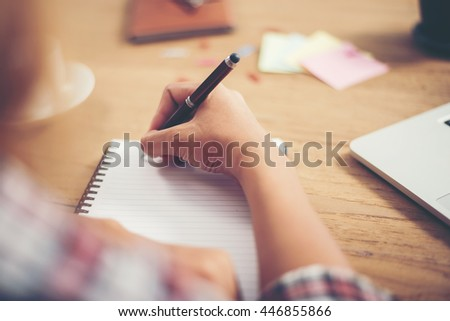 Young hipster woman writing and work in workplace.