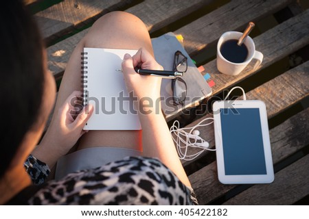 Young hipster woman writing journal on small notebook while sitting on wood bridge in morning time on weekend with high contrast sun lighting - stock photo
