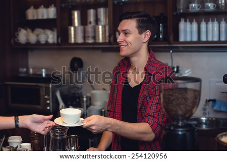 Young hipster working in cafe. Barista is passing an order to a customer smiling - stock photo