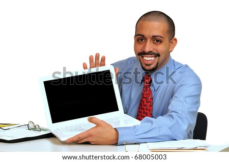 Young Hispanic business man seated at his desk holding his laptop, showing product message. - stock photo