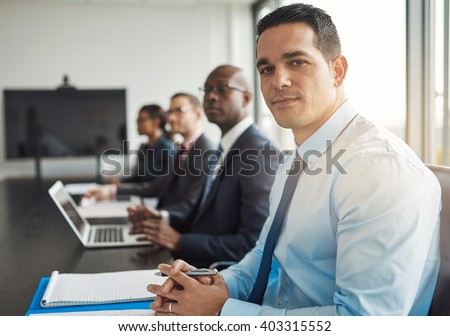 Young Hispanic businessman in a meeting with co-workers at the office sitting at a conference table turning to smile at the camera, diverse multiracial group of people - stock photo
