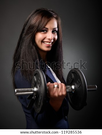 Young hispanic businesswoman showing her strength by lifting weights - stock photo