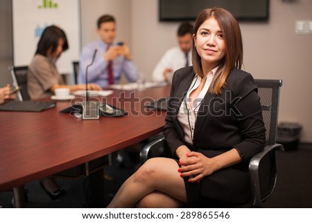 Young Hispanic businesswoman sitting in a meeting room with some of her colleagues - stock photo