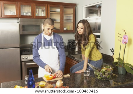 Young Hispanic couple chopping vegetables