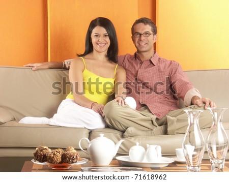 Young hispanic couple enjoying in a living room. Young couple enjoying in a house. - stock photo