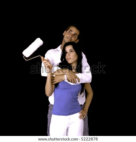 Young hispanic couple holding a painter roller - isolated over black