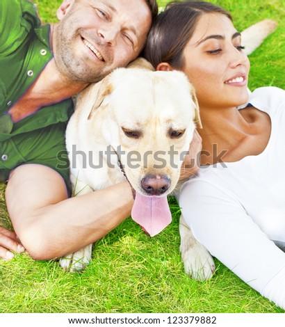 Young hispanic Couple lying with  white Dog - stock photo
