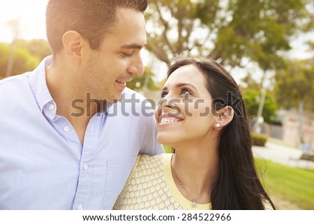 Young Hispanic Couple Walking In Park Together - stock photo