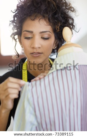Young hispanic female dressmaker adjusting clothes on tailoring mannequin and smiling. Vertical shape, head and shoulders