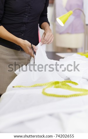 Young hispanic female dressmaker cutting white fabric for bridal gown. Vertical shape, front view, selective focus, copy space - stock photo
