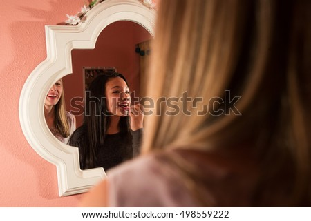 young hispanic girl applying lipstick in mirror