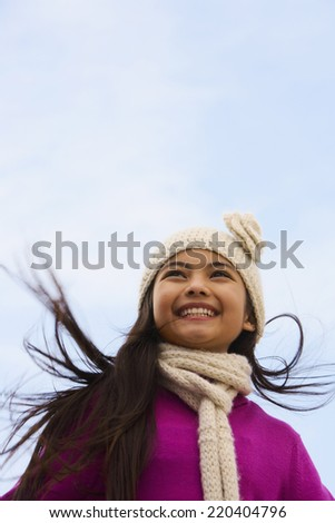Young Hispanic girl wearing hat and scarf outdoors - stock photo
