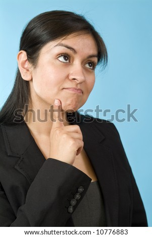 Young Hispanic girl with an inquisitive expression on her face taken front of a blue screen - stock photo