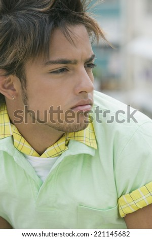 Young Hispanic man looking to side - stock photo