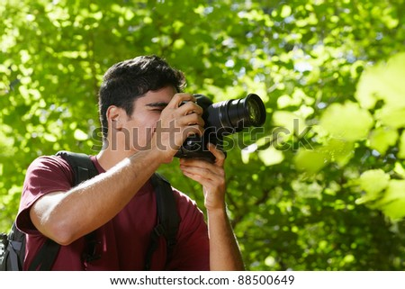 young hispanic man trekking among trees and taking pictures with dslr camera. Horizontal shape, side view, copy space - stock photo