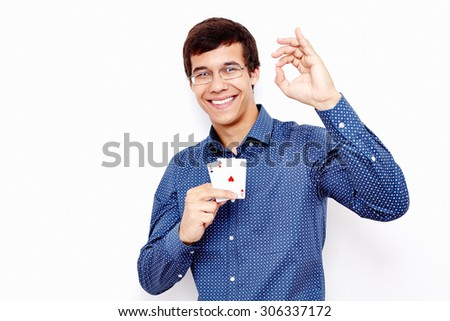 Young hispanic man wearing blue shirt and glasses holding two aces (clubs and hearts) in his hand and showing A-ok hand gesture with smile against white wall - gambling concept
