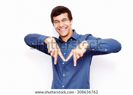 Young hispanic man wearing blue shirt and glasses showing M sign with his fingers and smiling against white wall - cities starting with M concept - stock photo