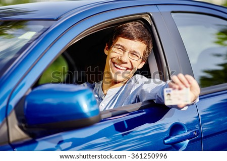 Young hispanic man wearing glasses and jeans shirt sitting behind wheel and holding out his driving license through car window - new drivers concept - stock photo