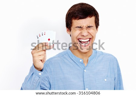 Young hispanic man wearing jeans shirt holding four aces (spades, hearts, clubs and diamonds) in his hand and loudly screaming against white wall - gambling winnings concept