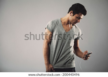 Young hispanic man with cell phone and earphones listening to music on grey background with copy space. Enjoying listening music on smartphone. - stock photo
