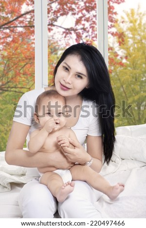 Young hispanic mother holding her baby girl while smiling at camera on bedroom - stock photo