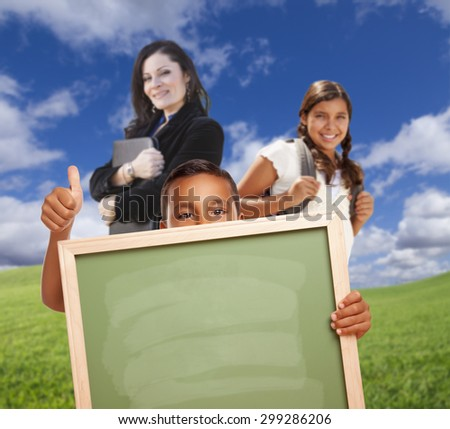Young Hispanic Students with Blank Chalk Board and Teacher Behind on Grass Field. - stock photo